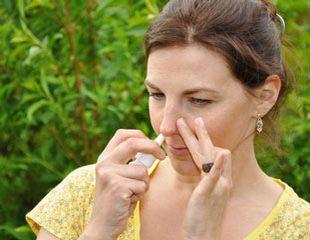Frau im Freien sprüht sich Cortison-Nasenspray gegen allergische Rhinitis ins rechte Nasenloch