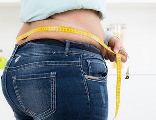 Frau misst ihren Bauchumfang mit einem Maßband