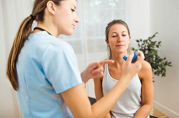 Eine Ärztin erklärt einer Frau die Verwendung eines Asthmasprays