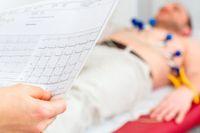 Patient bei einer Elektrokardiographie, im Vordergrund halten Hände den EKG-Ausdruck