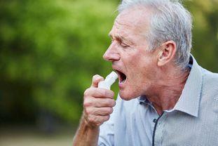Älterer Mann inhaliert im Freien Kortisonspray über einen Inhaler