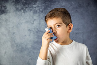 Bild eines Jungen, der einen Inhalator verwendet. Inhalatoren kann man zum Beispiel bei kindlichem Asthma verwenden. , zum Beispiel