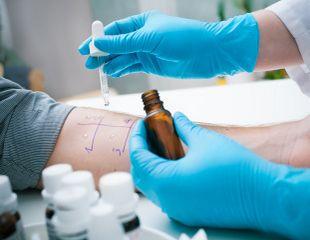 Der Pricktest wird dargestellt: eine Hand hält eine Pipette mit Testflüssigkeit. Diese tropft die Flüssigkeit auf den Unterarm eines Patientens.
