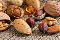 Verschiedene Nüsse mit und ohne Schale auf einem Leinensack