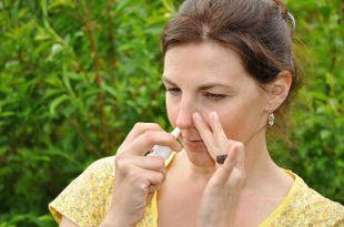 Frau sprüht Nasenspray in ihr rechtes Nasenloch