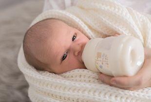 Baby in weißes Tuch eingehüllt trinkt aus einem Milchfläschchen - © fotolia