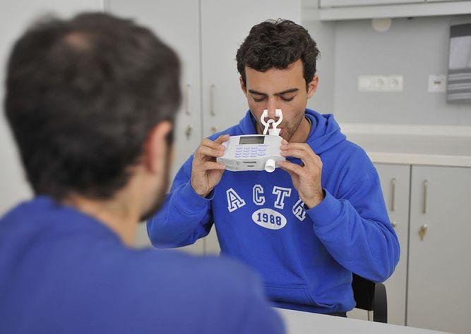 Mann beim Lungenfunktionstest zur Diagnose der exogen allergischen Alveolitis. Der junge Mann pustet in ein Spirometer, davor sitzt der Untersucher mit dem Rücken zum Betrachter