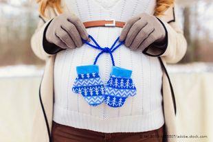 Schwangere Frau im Winter, Babyhandschuhen vor den Bauch hält - © tel.8033-6855507/adobe.stock.com