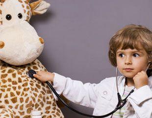 Kind im Arztkittel hört mit Stethoskop eine große Plüschgiraffe ab