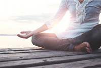 Eine Frau macht Yoga auf einem Steg, man sieht nur ihren Oberkörper und ihre Beine