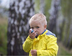 Kleiner blonder Junge in gelber Jacke inhaliert Asthmaspray im Freien.