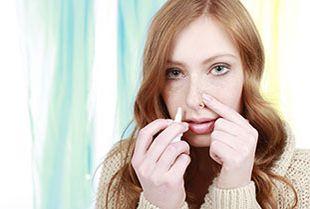 Frau inhaliert Cortison-Nasenspray gegen allergischen Schnupfen