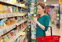 Frau prüft Zutatenliste mit Allergenkennzeichnung