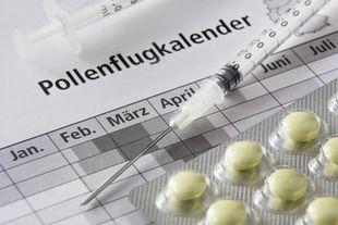 Auf einem Pollenkalender liegt eine Spritze und Tabletten, die man zur Hyposensibilisierung verwendet.