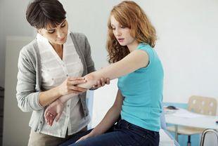 Ärztin untersucht Frau am Ellenbogen auf Neurodermitis und andere Hauterkrankungen