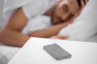 Im Vordergrund: schwarzes Smartphone auf weißem Tisch, im Hintergrund: Mann in weißem T-Shirt schläft in einem Bett