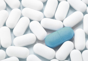eine blaue Pille unter vielen weißen Pillen
