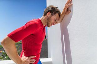 Junger Mann in rotem Sport-Shirt lehnt erschöpft mit dem linken Arm an einer Wand und lehnt die Stirn dagegen. Die rechte Hand stützt er in die Hüfte.